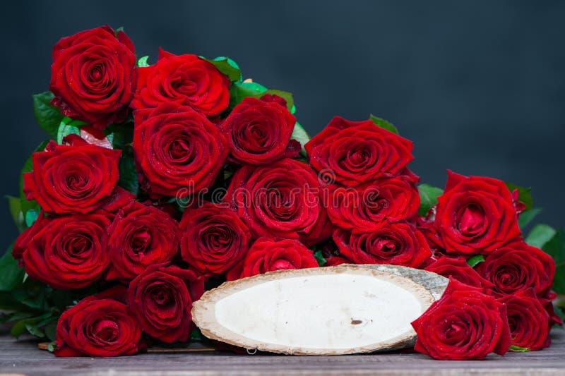 Stort fång av röda rosor med ett trästilfullt tecken för inskriften, utrymme för text förälskelse dag för valentin` s arkivbild