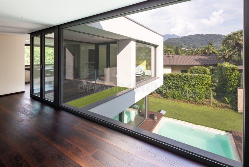 Stort fönster i hallet av den moderna villan som förbiser det privat arkivfoton