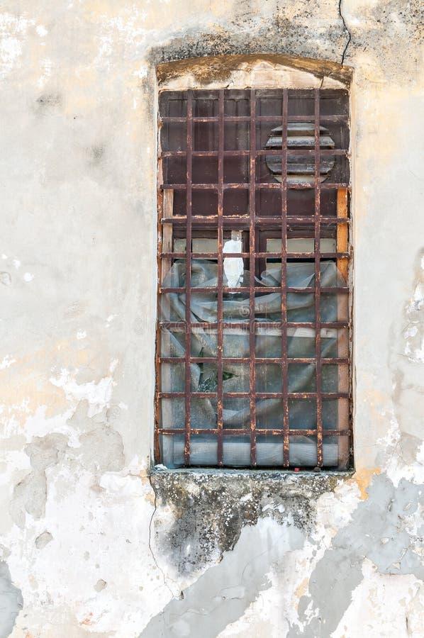 Stort gammalt fönster med rostiga metallsäkerhetsstänger eller spisgallrar på den övergav fängelsebyggnadsväggen royaltyfri bild