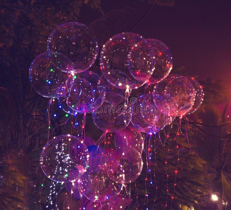 Stort härligt stelnar ballonger, målade ljus och ljusa kulor på natten royaltyfri fotografi