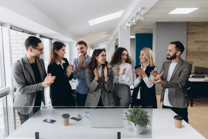Stort jobb! Det lyckade affärslaget applåderar deras händer i den moderna arbetsstationen som firar kapaciteten av nya produkten royaltyfri bild