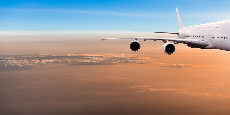 Stort kommersiellt flygplanflyg ovanför dramatiska moln arkivbild