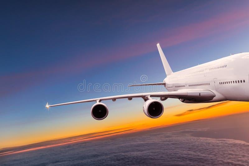 Stort kommersiellt flygplanflyg ovanför dramatiska moln fotografering för bildbyråer