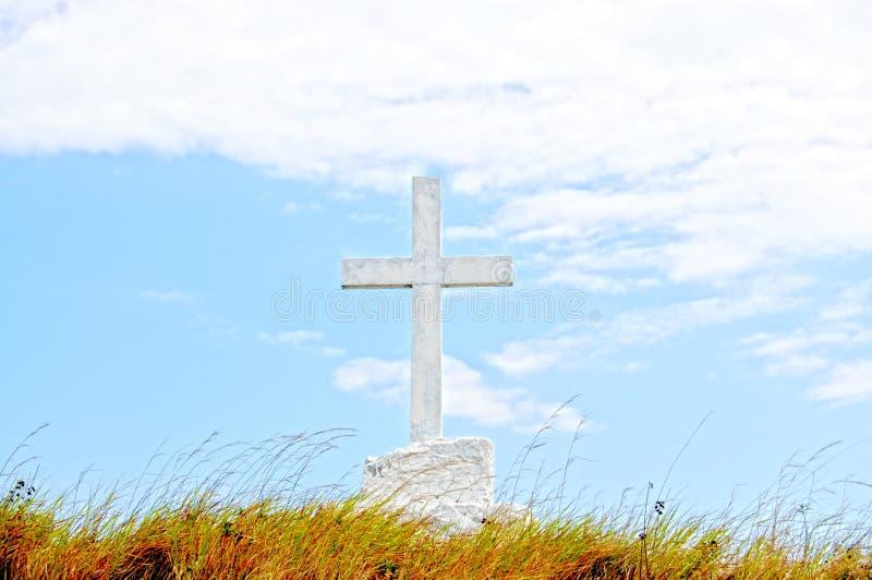 Stort kristenkors på ett fält mot en blå himmel royaltyfri fotografi