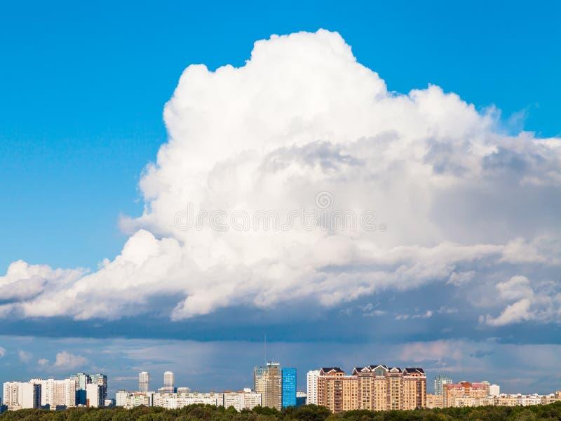 Stort lågt moln i blå himmel över stad i sommar arkivbild