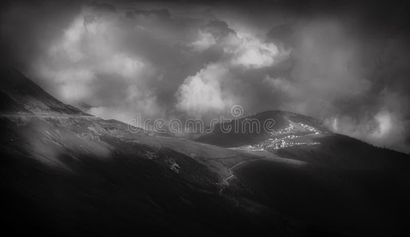 Stort landskap för berg med en by i avståndet, i en svartvit tolkning arkivbilder