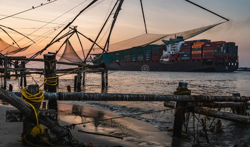 stort lastfartyg och gamla kinesiska fisknät under de guld- timmarna på fortet Kochi, Kerala, Indien royaltyfri bild