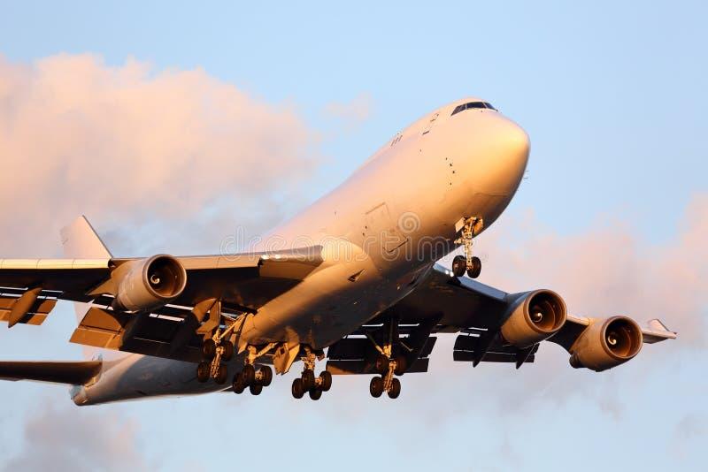 Stort lastflygplan som att närma sig flygplatsen på solnedgången royaltyfria bilder