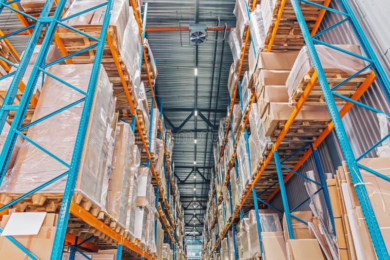Stort logistikhangarlager med lotthyllor eller kuggar med paletter av gods Industriell sändnings arkivbilder