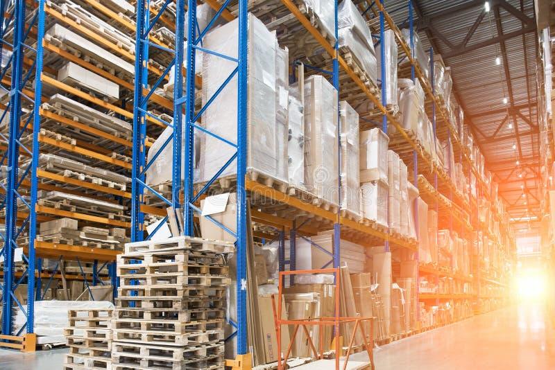 Stort logistikhangarlager med lotthyllor eller kuggar med paletter av gods och solljuseffekt royaltyfria bilder