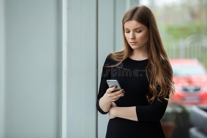 Stort meddelande! Gladlynt ung härlig kvinna som använder hennes smartphone med leende, medan stå på hennes kontor arkivfoton