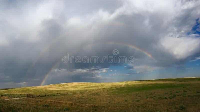 Stort moln för himmeldubblettregnbåge arkivfoto