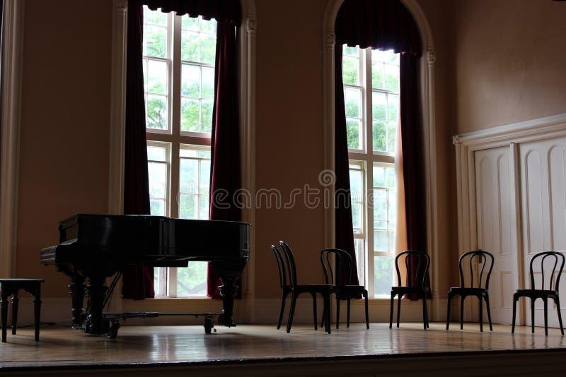 Stort piano som omges av trästolar på etapp av mötesrum, Oneida Community Mansion House, Oneida, New York, 2018 arkivfoto