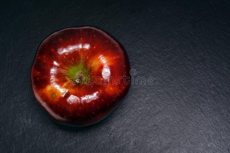 Stort rött äpple på svart arkivbild