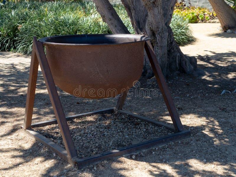 Stort rostigt stålkrukasammanträde i skugga av ett soligt läge arkivfoto