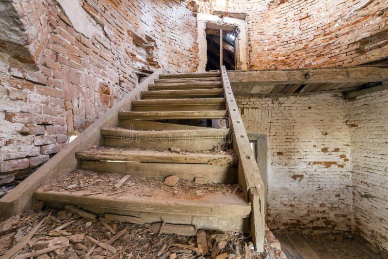 Stort rymligt lämnat kvar tomt källarerum av forntida byggnad eller slott med spruckna packade tegelstenväggar, det smutsiga golv arkivbilder