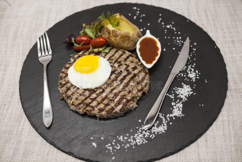 Stort saftigt grillat biff marmorerat nötkött med ägget bakade potatisar med grillfestsås Tjänat som på en stenplatta med en gaff royaltyfri foto