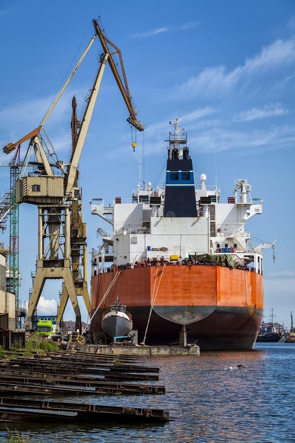 Stort skepp och ett litet fartyg i gården arkivbild
