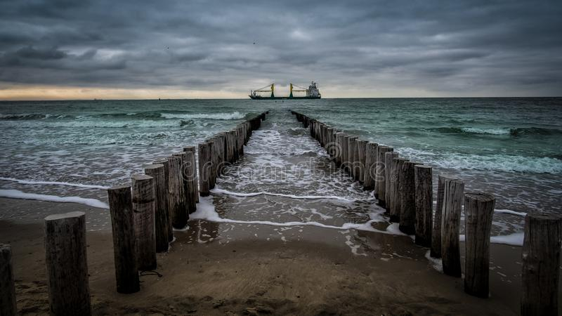 Stort skepp som korsar träpir under molnigt väder på stranden i Vlissingen, Zeeland, Holland, Nederländerna royaltyfri fotografi