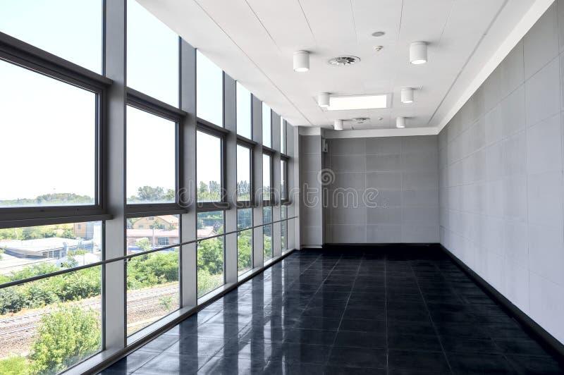 Stort tomt kontorsutrymme med fönsterväggen Ljus belysning för dag royaltyfria foton