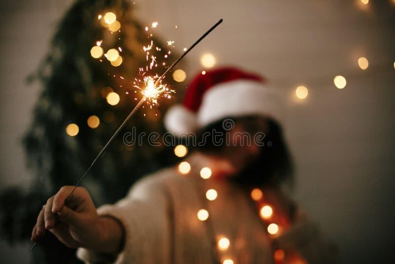 Stort tomtebloss som bränner i hand av den stilfulla flickan i den santa hatten på bakgrund av modernt ljus för julträd i mörkt r arkivbilder