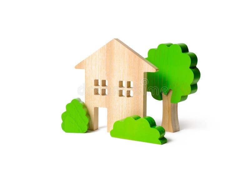 Stort två-berättelse hus som omges av buskar och träd på en isolerad bakgrund Urbanism och stads- landskap _ royaltyfri fotografi