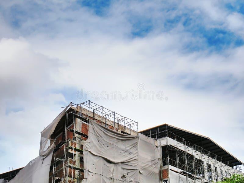 Stort under konstruktionsbyggnad med ramar och räkningar mot molnig blå himmel arkivbilder