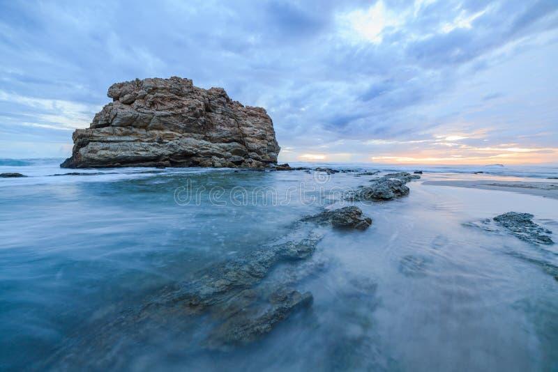 Stort vagga lång exponering för strandsolnedgången fotografering för bildbyråer