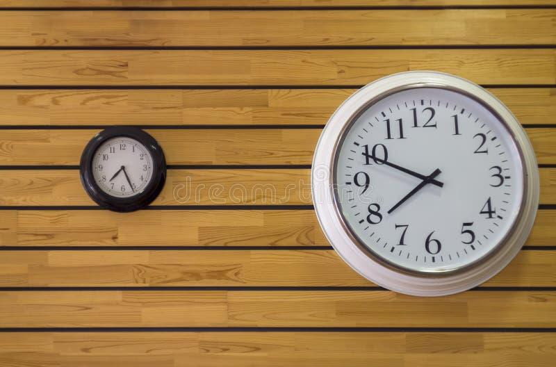 Stort vitt runt klockaslut upp och en svart liten klocka med pilar på den gula väggen av träplankor Horisontal fodrar arkivbild