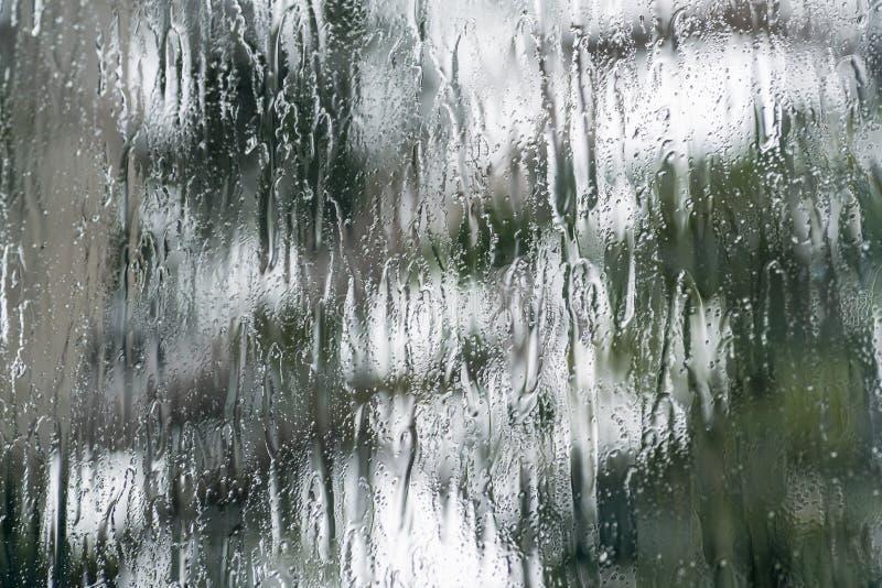 Stortbui die het venster behandelen tijdens een onweer; vage boomvorm zichtbaar op de achtergrond; abstracte achtergrond royalty-vrije stock fotografie