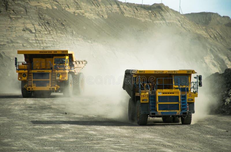 Stortplaatsvrachtwagens op een kolenmijn op een Zonnige dag stock afbeeldingen