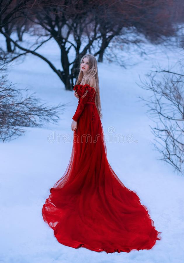 Story of frozen fairy tale, wonderful pretty blonde princess in gorgeous adorable royal maroon magical dress of red and royalty free stock photos