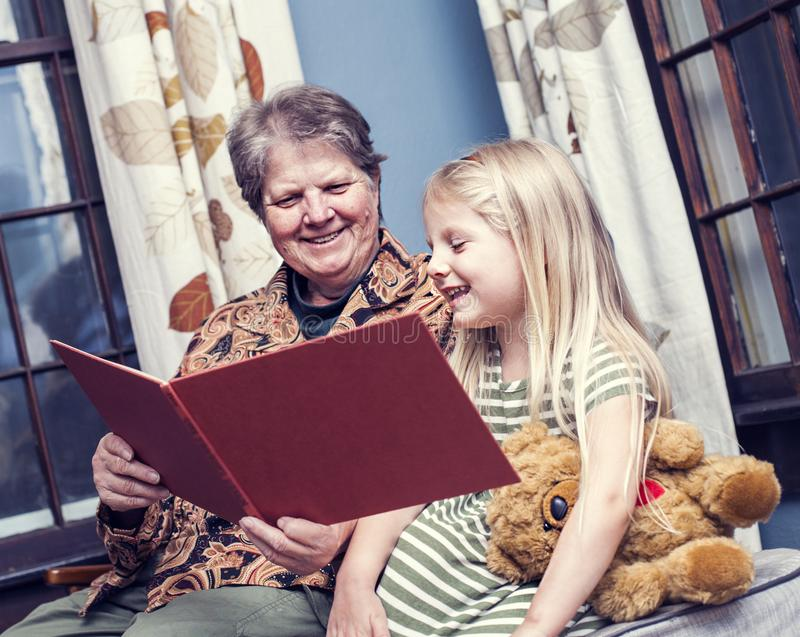 Story for night. Grandmother reading night story to her granddaughter at home stock images
