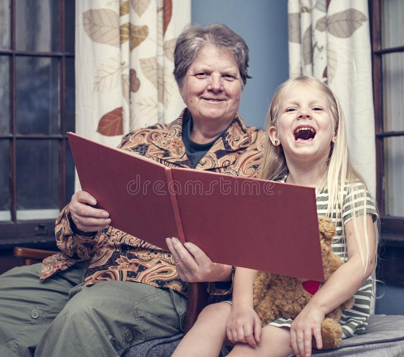 Story for night. Grandmother reading night story to her granddaughter at home royalty free stock images
