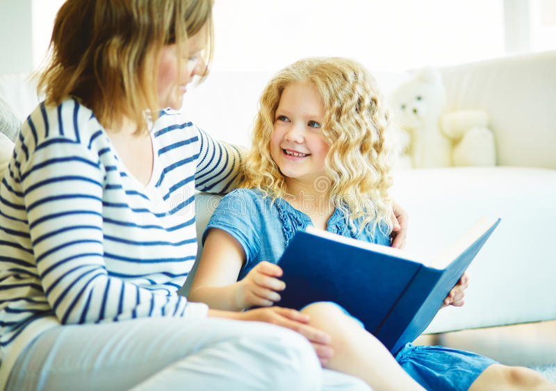 Story telling. Portrait of cute girl listening to her mother telling an interesting story at home royalty free stock photography