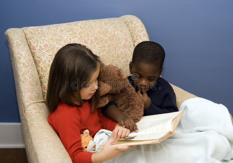 Story Time. Two small children reading a story in a big, comfortable chair. Diversity