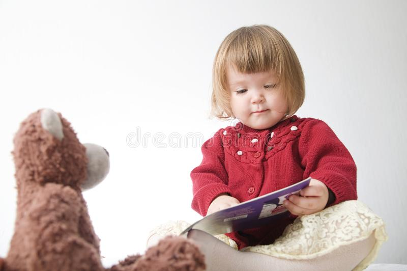 Story time. Little girl playing school with toys teddy bear and doll.  children education and development, happy childhood royalty free stock photography
