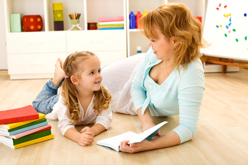 Story time - little girl and woman reading a book. Story time - woman reading a tale to her little girl stock photos