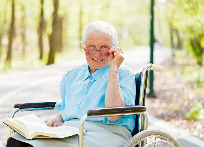 Storyteller Elderly Lady. Kind elderly lady in wheelchair with book in hands reading story outdoors royalty free stock images
