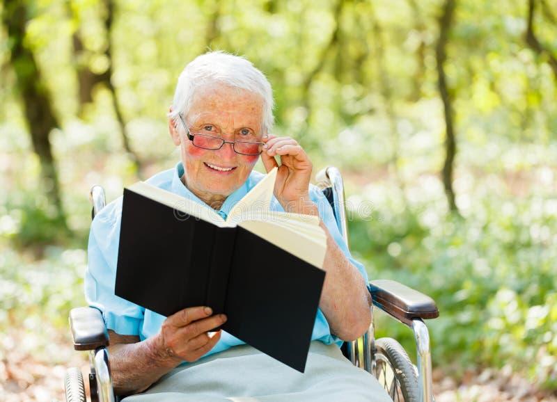 Storyteller Elderly. Elderly woman in wheelchair holding and reading a book stock photos