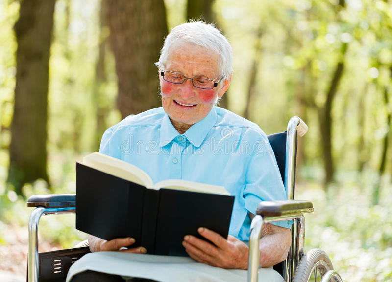 Storyteller Elderly. Elderly woman in wheelchair holding and reading a book royalty free stock image