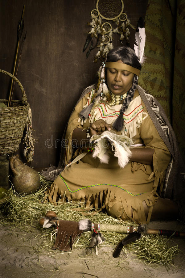 Storyteller squaw. Weathered mature tribal female storyteller talking about heroic times royalty free stock photography