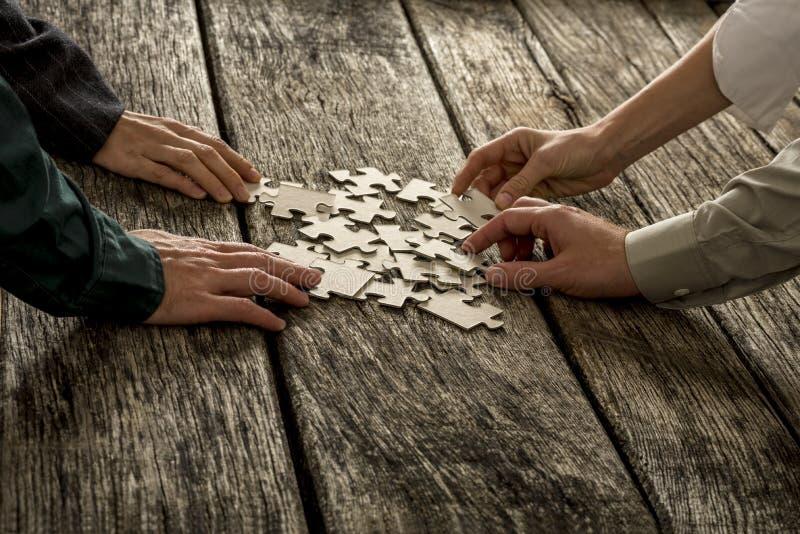 Stos łamigłówka kawałki kłama na drewnianym biurku z cztery rękami dosięga zdjęcia royalty free