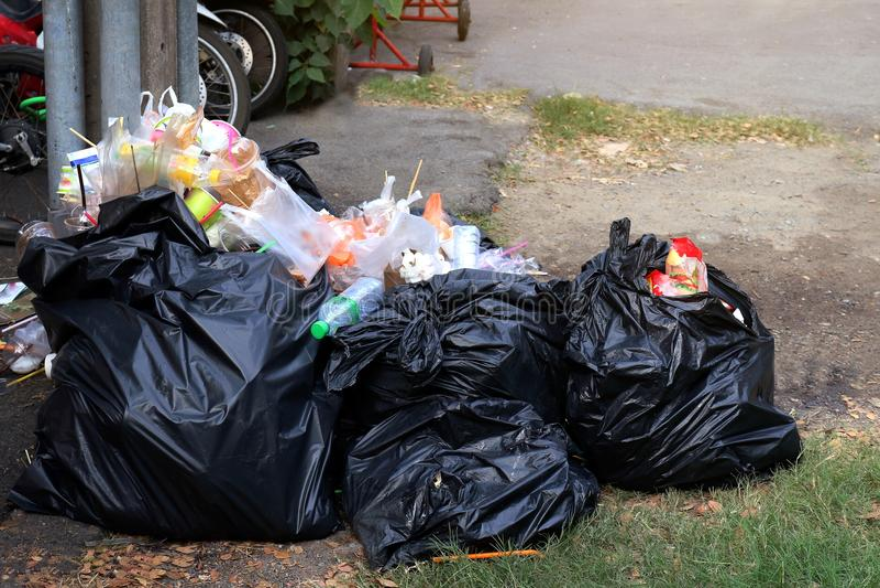 Stos Śmieciarska plastikowa czerni i grata torba marnotrawi dużo na podłoga, zanieczyszczenie grata, klingerytu odpady i torby ta zdjęcia royalty free
