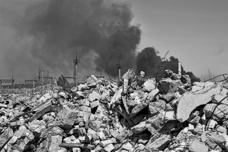 Stos betonowy gruz z sterczącym rebar na tle gęsty czerń dym w niebie Tło zdjęcia stock