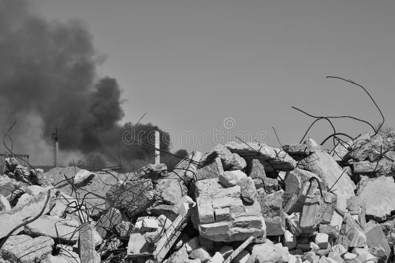 Stos betonowy gruz z sterczącym rebar na tle gęsty czerń dym w niebie Tło fotografia stock