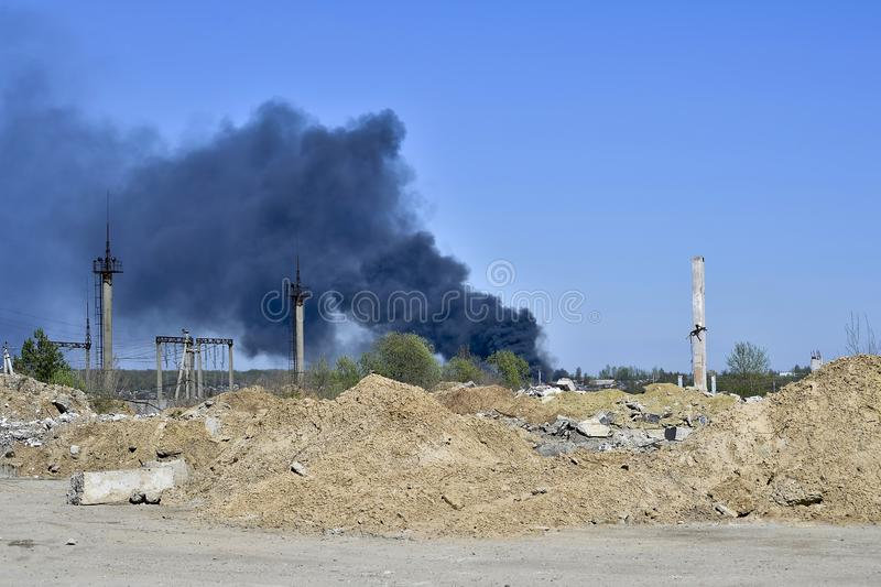 Stos betonowy gruz z sterczącym rebar na tle gęsty czerń dym w niebieskim niebie obraz royalty free