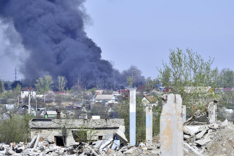 Stos betonowy gruz z sterczącym rebar na tle gęsty czerń dym w niebieskim niebie zdjęcie royalty free