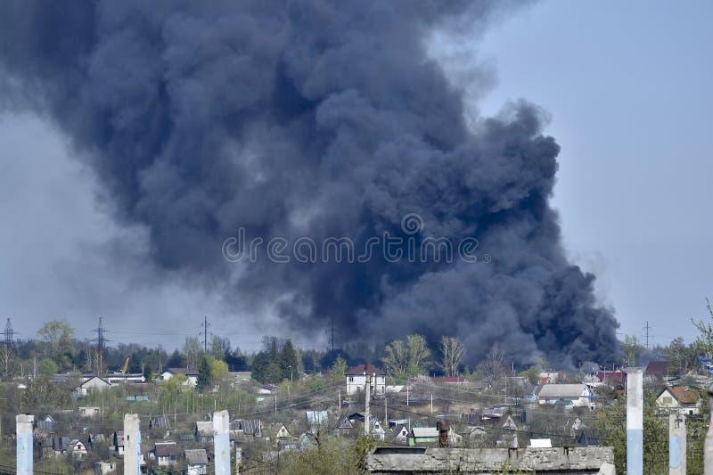 Stos betonowy gruz z sterczącym rebar na tle gęsty czerń dym w niebieskim niebie obraz stock