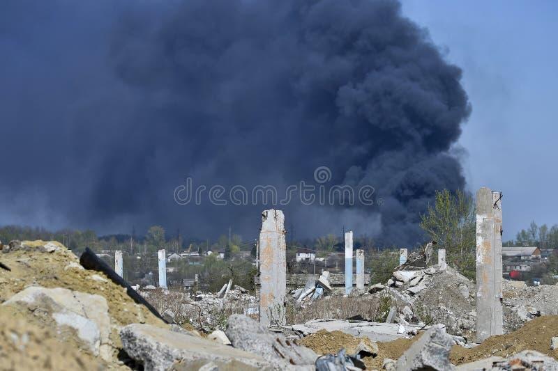 Stos betonowy gruz z sterczącym rebar na tle gęsty czerń dym w niebieskim niebie zdjęcia royalty free